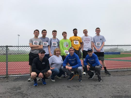 The Kennard-Dale cross country team poses for a picture with Gloria Crothers at the 2019 memorial 5K in honor of her son, Sgt. Mike Heede.