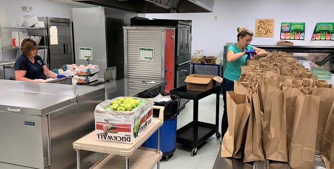 Volunteers prepare bags of food for distribution.