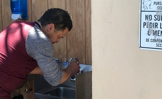 A man washes his hands at a newly installed sink before receiving lunch at Dorothy's Place. Staff there are mandating everyone wash their hands before receiving food.