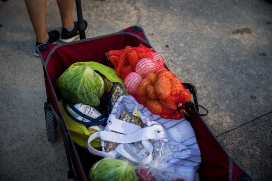 A cart full of food is rolled to someone's car at Central Texas Food Bank mobile food pantry in Kyle in August.
