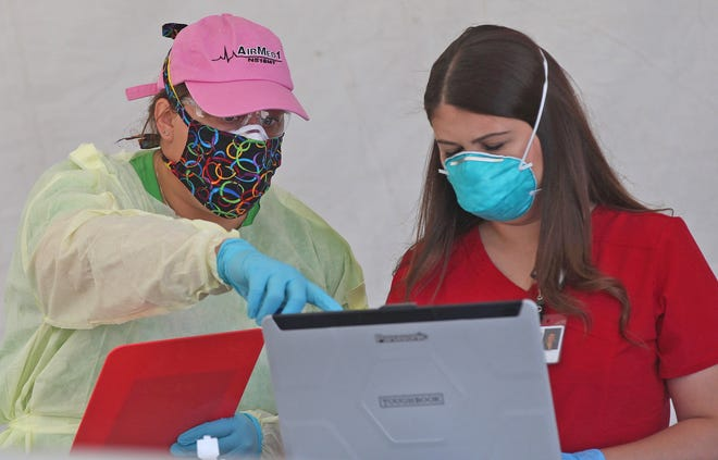 Health care professionals with Shannon Medical Center work on a computer at a drive thru testing facility Thursday, April 16, 2020.