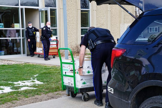 Sioux Falls police officers load boxes of cleaning supplies donated by the Sioux Falls School District this week to help support officers working during the coronavirus pandemic.