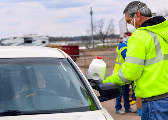 Phil T. hands a gallon of milk to a driver on Thursday, April 16, at the Lyons Fairgrounds in Sioux Falls. Feeding South Dakota, the Helpline Center, Faith Temple Food Giveaway, Corona Help Sioux Falls and the Salvation Army are partnering to give groceries to families in need during the coronavirus pandemic.