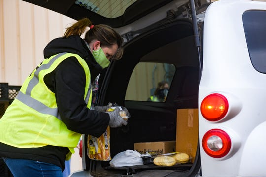 Natasha Tassler places bread and desserts in the back of car on Thursday, April 16, at the Lyons Fairgrounds in Sioux Falls.Feeding South Dakota, the Helpline Center, Faith Temple Food Giveaway, Corona Help Sioux Falls and the Salvation Army are partnering to give groceries to families in need during the coronavirus pandemic.