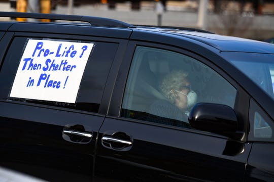 A woman wears a mask while sitting in her car in the parking lot with a sign encouraging a stay-at-home order as city councilors arrived for their weekly meeting on Wednesday, April 15, at Carnegie Town Hall in Sioux Falls.