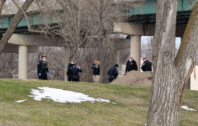 Police officers and the Crime Scene Investigation team inspect a the scene of a body found near the Big Sioux River on Wednesday evening, April 15, under the 10th street viaducts in Sioux Falls.