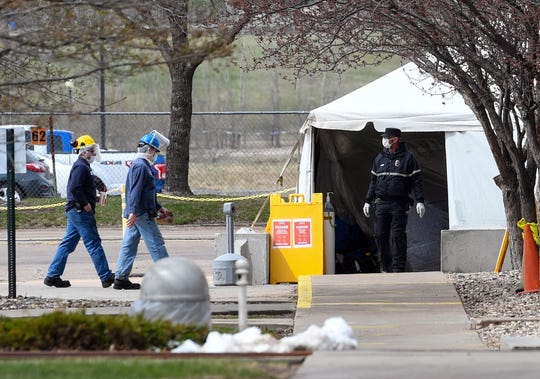 People enter Smithfield Foods, Inc. through a screening tent on Thursday, April 16, in Sioux Falls. The plant is currently closed due to the coronavirus outbreak.