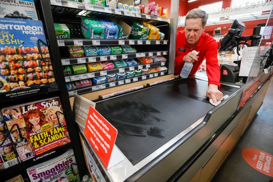 David Frost, an assistant manager at Hy-Vee, sanitizes the belt between customers at the check-out counter to help protect customers from the coronavirus on Wednesday, April 15, 2020.
