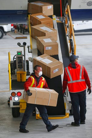 """A plane filled with personal protective equipment is unloaded at the Delta Hanger Wednesday, April 15, 2020, at the Salt Lake International Airport. The first of several planes filled with personal protective equipment touched down in Utah, delivering masks and eye protection for health care workers throughout the state. """"We are in a wartime environment. (AP Photo/Rick Bowmer)"""