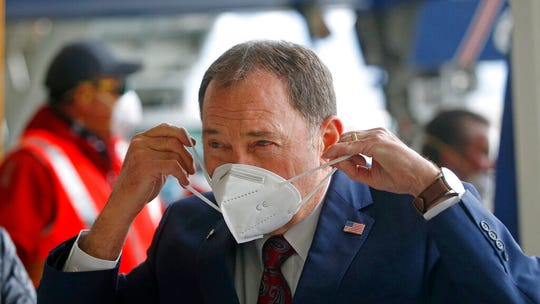 Utah Gov. Gary Herbert puts on a mask that came off a plane filled with personal protective equipment at the Delta Hanger Wednesday, April 15, 2020, at the Salt Lake International Airport. The first of several planes filled with personal protective equipment touched down in Utah, delivering masks and eye protection for health care workers throughout the state. (AP Photo/Rick Bowmer)