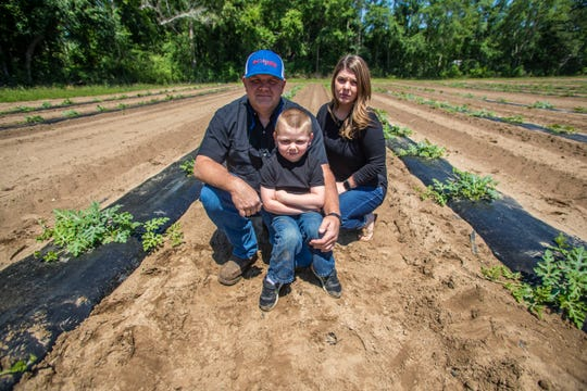 Jason Vinson, 43, has been growing watermelon for 21 years. As the economy is threatened from all angles, the lifelong Jefferson County resident is facing uncertainty with this main source of income as his buyers' businesses are threatened. Vinson poses for a photo with his wife Jessica and their 5-year-old son Jase.