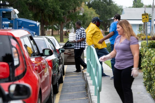 "NAACP St. Lucie County member Mario Wilcox (left) delivers boxes of free food to a waiting family as volunteers, NAACP board members and Sweetie's Diner staff serve a line of cars wrapped around the diner Thursday, April 16, 2020, in Fort Pierce. ""We found out people were really hungry,"" said NAACP St. Lucie County President George Collins (third from left). ""When we all come together we can get it done. We have people coming together and realizing what a neighbor is."""