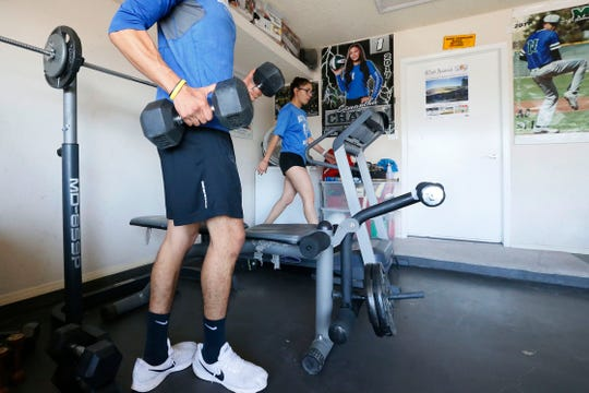 Samantha Chavez and Anthony Chavez work out in their garage Tuesday, April 14, in El Paso. Samantha is a softball player at Montwood High School and is going to play at Sul Ross State University in college next year. Anthony is a junior at St. Mary's University and is a pitcher on the baseball team.
