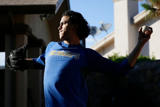 Anthony Chavez practices pitching with his dad in their backyard Tuesday, April 14, in El Paso. Anthony is a baseball player at St. Mary's University. Anthony is a junior at St. Mary's University and is a pitcher on the baseball team.