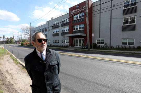 Derek Hudson of Larchmont stands across from The Enclave at Rye Rehabilitation and Nursing Center in Port Chester April 16, 2020. Hudson's mother Myrian Hudson as been a resident at the nursing home for three years. He says that the home has not been communicative with him regarding the status of residents and staff who may have COVID-19. He also says that he has not been able to speak with his mother for two weeks, following a FaceTime conversation that he had with her on a borrowed cell phone.