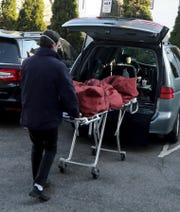 Funeral director Mark Flower, manager of Flower Funeral Home in Yonkers, removes a body he had just picked up from the New York City Medical Examiner's office from his van outside his funeral home on April 15, 2020.