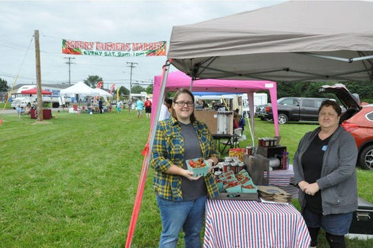 Ali Dziedzinski (left) and Melody Lasana from Hundred Acre Farms sell strawberries and other fresh produce last year at the Smyrna Farmers Market on Glenwood Avenue next to Glenwood Cemetery, across from American Legion Post 14.