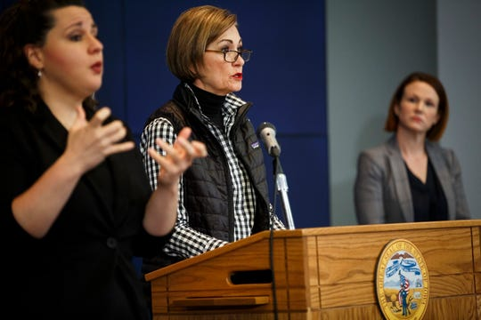 Iowa Gov. Kim Reynolds, center, speaks during a news conference on COVID-19 at the State Emergency Operations Center, Wednesday, April 15, 2020, in Johnston, Iowa.