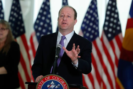 Colorado Gov. Jared Polis makes a point during a news conference to update the state's efforts in battling the spread of the new coronavirus in the governor's mansion Monday, April 13, 2020, in Denver.