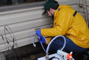 USGS scientist Joel Stokdyk collects a homeowner water sample in March, 2020.