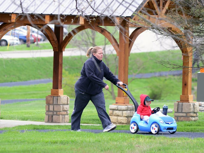 Kelsey Mobley walks with her child at the Genesis Fitness Trail. With gyms closed due to COVID-19, many have turned to walking outside or other activities to maintain wellness.