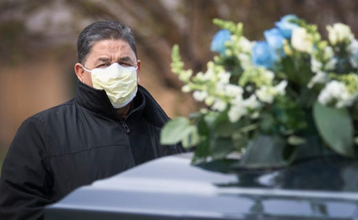 A mourner attends the funeral of Saul Sanchez, a longtime JBS employee that died of the coronavirus disease, at Sunset Memorial Cemetery in Greeley, Colo. on Apr 15, 2020.