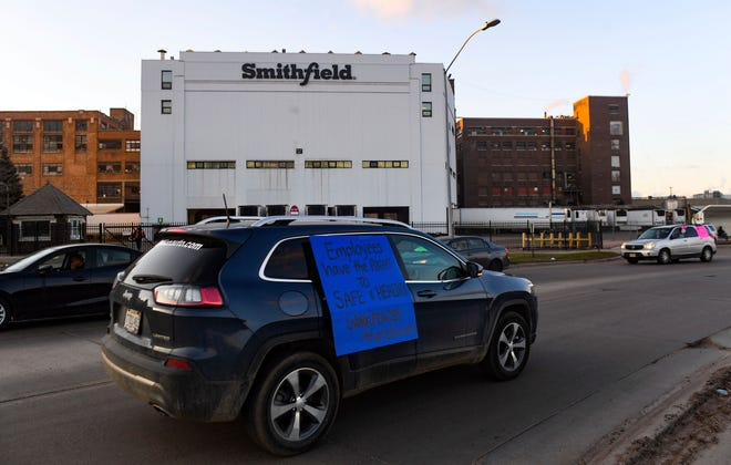 A car sporting a sign calling for a safe and healthy workplace drives past Smithfield Foods, Inc. in Sioux Falls on April 9, 2020 during a protest on behalf of employees after many workers complained of unsafe working conditions due to the COVID-19 outbreak. The pork processing plant in South Dakota is closing temporarily after more than 80 employees tested positive for the coronavirus.