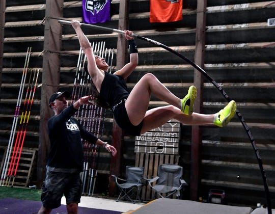 Brit Pursley gives his daughter Kaydi an assist as she practices pole vaulting inside her grandfather's grain warehouse Wednesday. When Kaydi vaults at Abilene Christian University, she will be following in the footsteps of her uncle Brad who was a national champion there in the same sport.