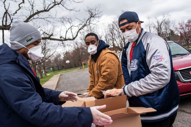 Damon Brown, Kelley Blythe and Kevin Adams from the Battle Creek nonprofit, R.I.S.E., distribute food during economic hardship brought upon by the COVID-19 pandemic on Friday, April 10, 2020 at Washington Heights Methodist Church.