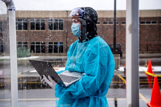 Emergency medicine research assistant Jacob Winkel conducts drive-through COVID-19 testing for first responders and medical professionals, an initiative of Wayne State Physician Group and ACCESS, on Friday, April 17, 2020 outside of City Hall in Battle Creek.