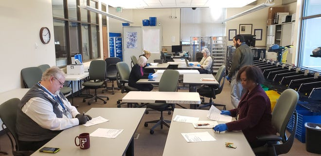 Members of the Kitsap County Canvassing Board on March 20 certify the Feb. 11, 2020, special election wearing gloves and sitting at a distance to prevent the spread of coronavirus.