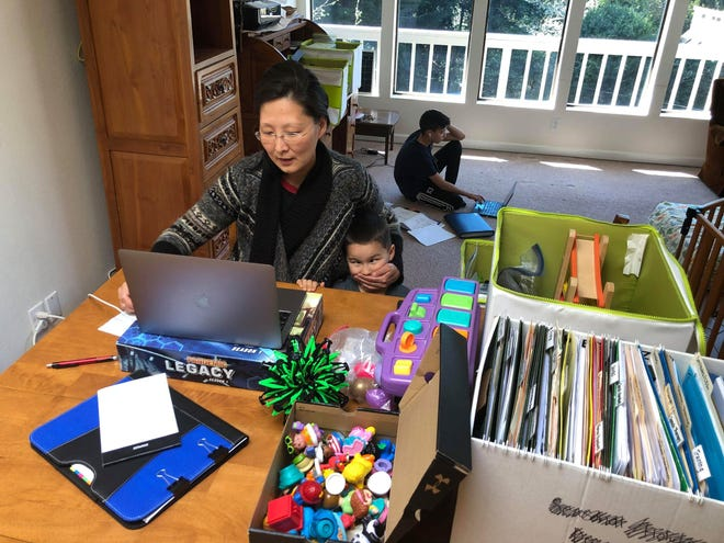 Holly Ridge Center speech-language pathologist Hope Stevens works with a client from home while her children play and study.