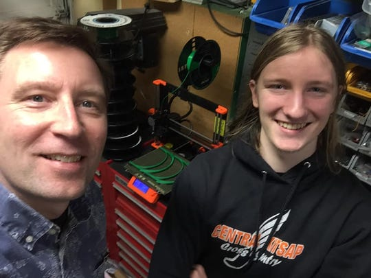 """Tim Putaansuu, left, and his son, William, are currently churning out 26 face shields a day on one printer. """"We are proud to be helping out those on the front lines of this pandemic,"""" Tim said."""