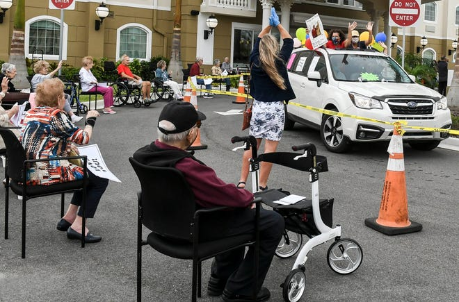Relatives and loved ones wave to residents of Chateau Madeleine senior living and memory care facility during a drive-thru parade Friday, April 17, 2020 in Melbourne. Mandatory Credit: Craig Bailey/FLORIDA TODAY via USA TODAY NETWORK