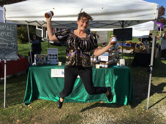 Marikje Shelmandine, 11 weeks pregnant, jumps for joy at Stowe Farmers Market late 2019 after taking over father's sauce business, It's Arthur's Fault, in his memory.