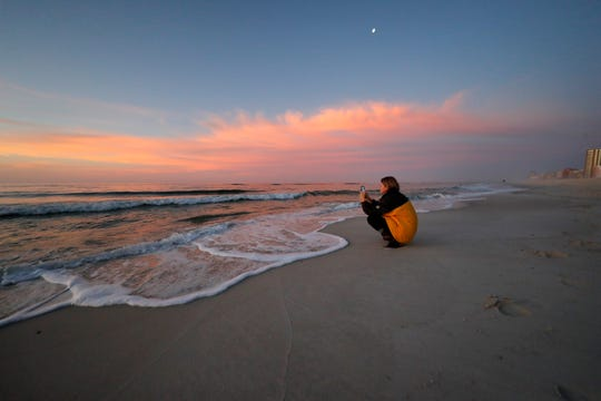 In this March 13, 2020, file photo, Rachel Bobo, of Orange Beach, Ala., takes photos of the sunrise on the Gulf of Mexico in Gulf Shores, Ala. The spring of coronavirus feels a lot like the summer of oil to residents along the Gulf Coast. Bars and restaurants are empty in Florida because of an invisible threat nearly a decade after the BP oil spill ravaged the region from the ocean floor up, and condominium reservations have taken a nosedive in Alabama. (AP Photo/Gerald Herbert, File)