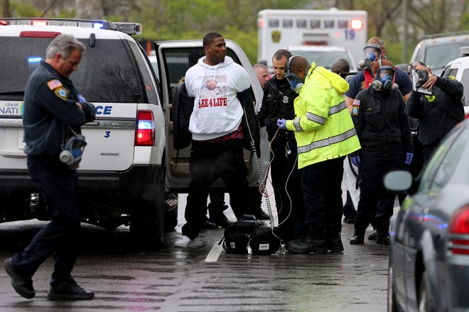 A man, who was detained and then later released, is examined by fire personnel as authorities respond to a crash in the 1900 block of Westwood Northern Boulevard, Friday, April 17, 2020, in Cincinnati. A victim from an unrelated shooting alerted an officer responding to the crash and was taken to University of Cincinnati Medical Center.