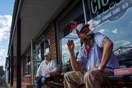 Jason Ferguson, right, and Beverly Huff, left, hang out with a group of regulars that moved outside to practice social distancing at Big Boy's Cigar and Lounge in Dickson, Tenn., on Wednesday, April 15, 2020.