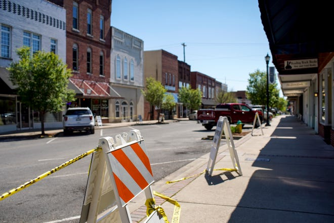 Signage advertising pick-up locations and parking spots occupies areas on the sidewalk of an empty Main St in Dickson, Tenn., on Wednesday, April 15, 2020.