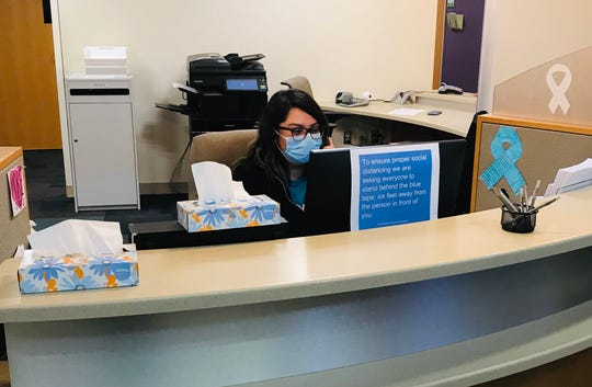 Adriana Mendoza, a customer service representative at CHASS Center Detroit, takes calls from nervous patients as she and other staff try to keep their own stresses in check during the pandemic.