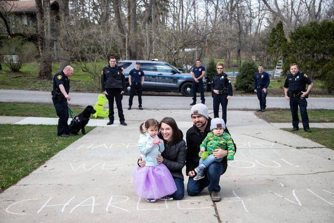 MacKenzie Meador, 4 with her mother Molly, father Jeff and brother Ethan, 1, pose for a photo with Birmingham Police officers and firefighters outside of their home in Birmingham on April 16, 2020.