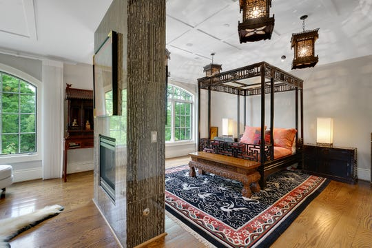 The owner's sleeping room is partly divided by a structure that holds a two-way fireplace and a TV screen. The partly screened space to the left is set up as a luxurious woman's dressing room.