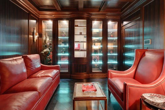 Exquisite carpentry in the small cigar room was done with walnut and Macassar cq ebony. Pushing one button starts a three-stage air purifying system that ends with 30 minutes of ozone. The center of the five slim, lighted cabinets is a humidor.