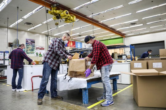 Nathan Wolf, 35, of Sterling Heights and Paul Elliott, 52, of Casco Township are normally wood model makers at the General Motors Design Studio at the Warren Technical Center but are using their expertise Friday to make and pack aerosol boxes for medical professionals.