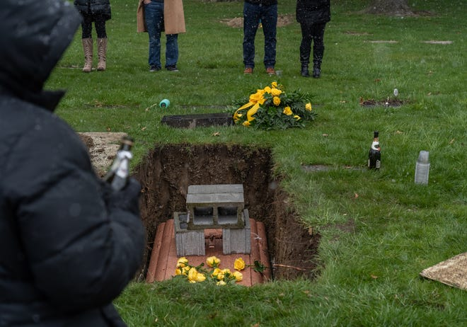 """Family of the late 90-year-old Janice """"Granny"""" Severini, of Shelby Township, stand around her gravesite on April 17, 2020, at Resurrection Cemetery in Clinton Township after the family waited for the vault with her casket to be lowered into the ground to say their last goodbyes. Severini passed due to COVID-19 and the plans she had made for her funeral services and events were canceled due to the circumstances leaving the family without a funeral or procession mourning after the casket was lowered into the ground at the cemetery."""
