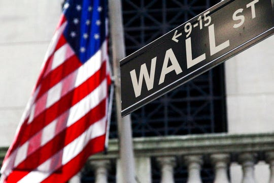 This Monday, July 15, 2013, file photo shows the American flag and Wall Street sign outside the New York Stock Exchange.  Stocks are rising at the opening of trading on Wall Street Friday as investors rally around signs that more governments are planning phased re-openings of their economies.