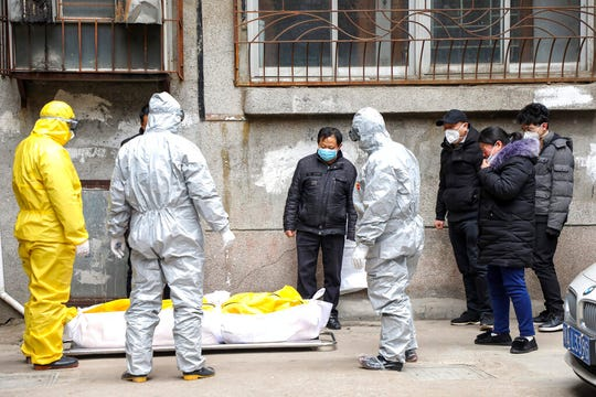 In this Feb. 1, 2020, file photo, funeral home workers remove the body of a person suspected to have died from the coronavirus outbreak from a residential building in Wuhan in central China's Hubei Province.