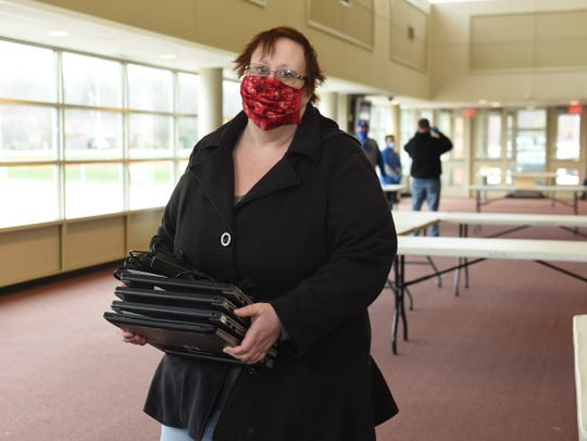 Shannon Wade of Shelby Township picks up four laptops for her kids during a technology distribution at Henry Ford II High School in Sterling Heights. UCS is providing around 2,000 computers to families to support online learning initiatives.
