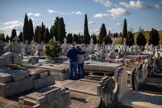 Two people attend a burial of a relative at a Madrid cemetery during the coronavirus outbreak in Madrid, Spain, March 27, 2020.