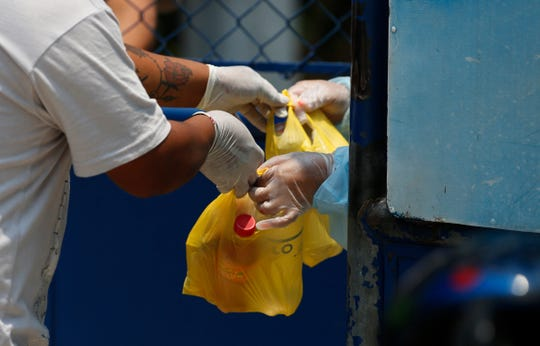 A health worker, right, receives food from a resident, at an athletic dorm facility being used to house Guatemalans deported from the U.S.